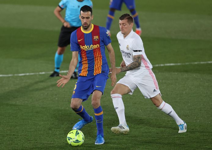 Busquets and Kroos compete for the ball.